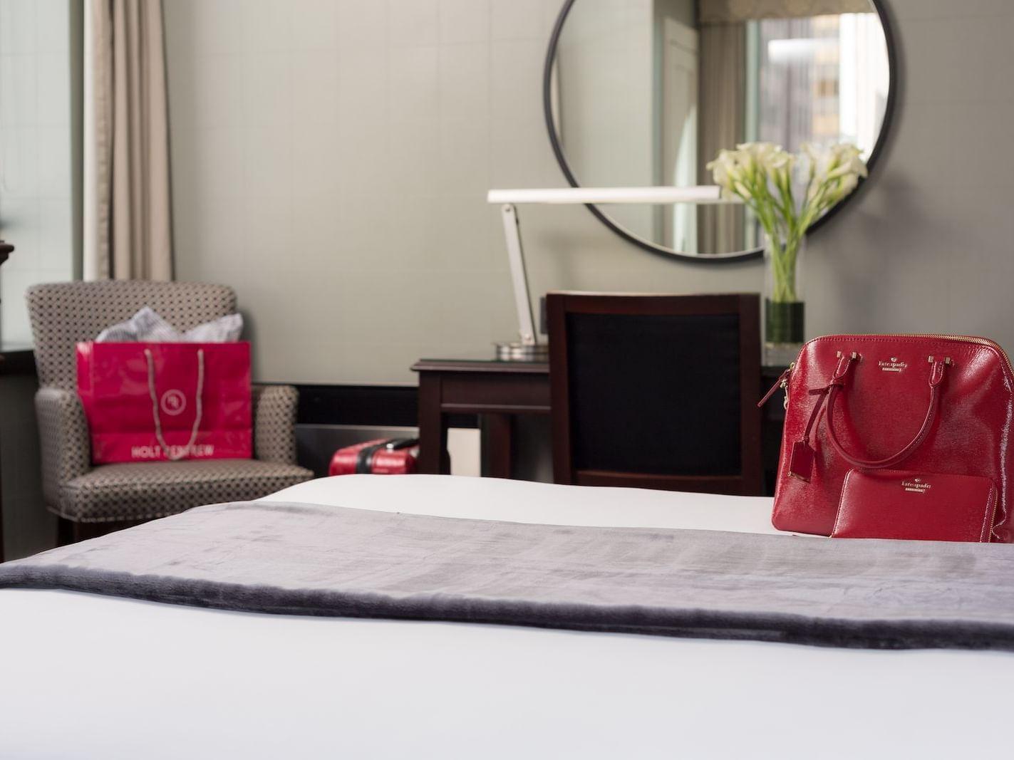 red bag on queen bed facing circular mirror