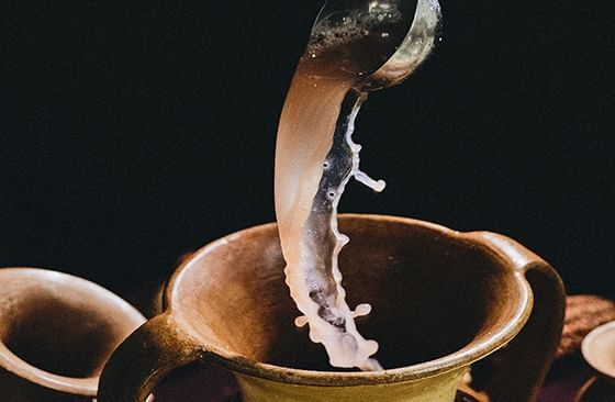 An image of a drink pouring to a two handled cup at Hotel Sumaq
