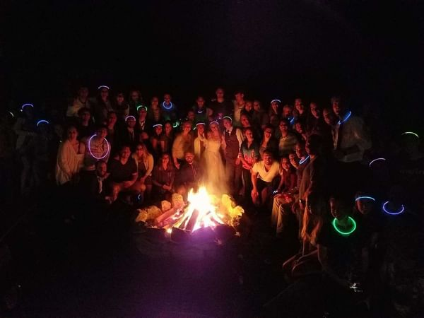 Group gathered around a lit firepit.