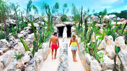 A couple walking down the Xenses park near The Reef Resorts