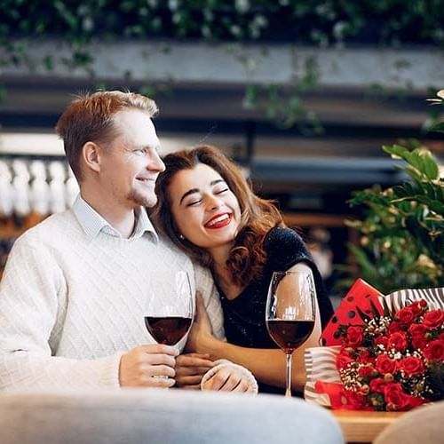 a woman hugging her fiance while drinking wine