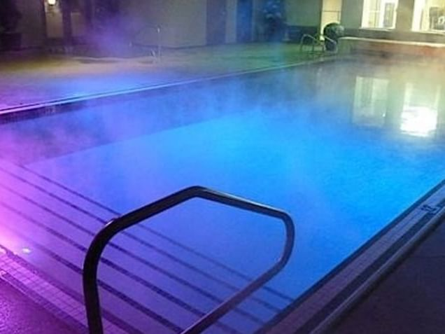 Pool & Hot Tub with lights at night in Carriage House Hotel
