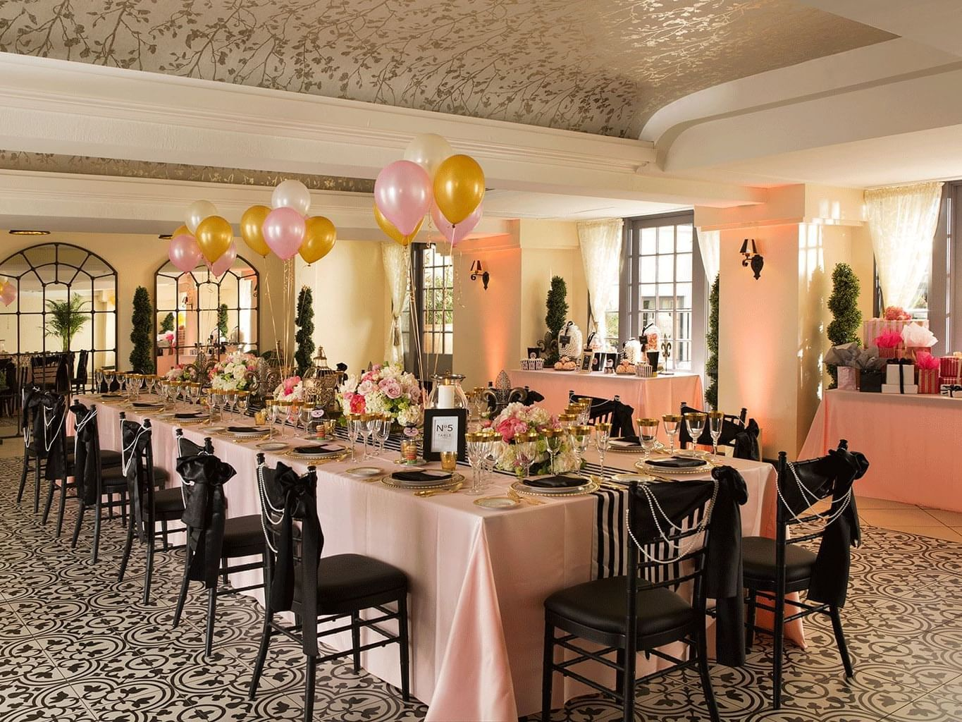 ballroom with large table with pink tablecloth and black chairs