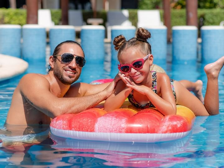 A girl playing with her father in pool at The Reef Coco Beach