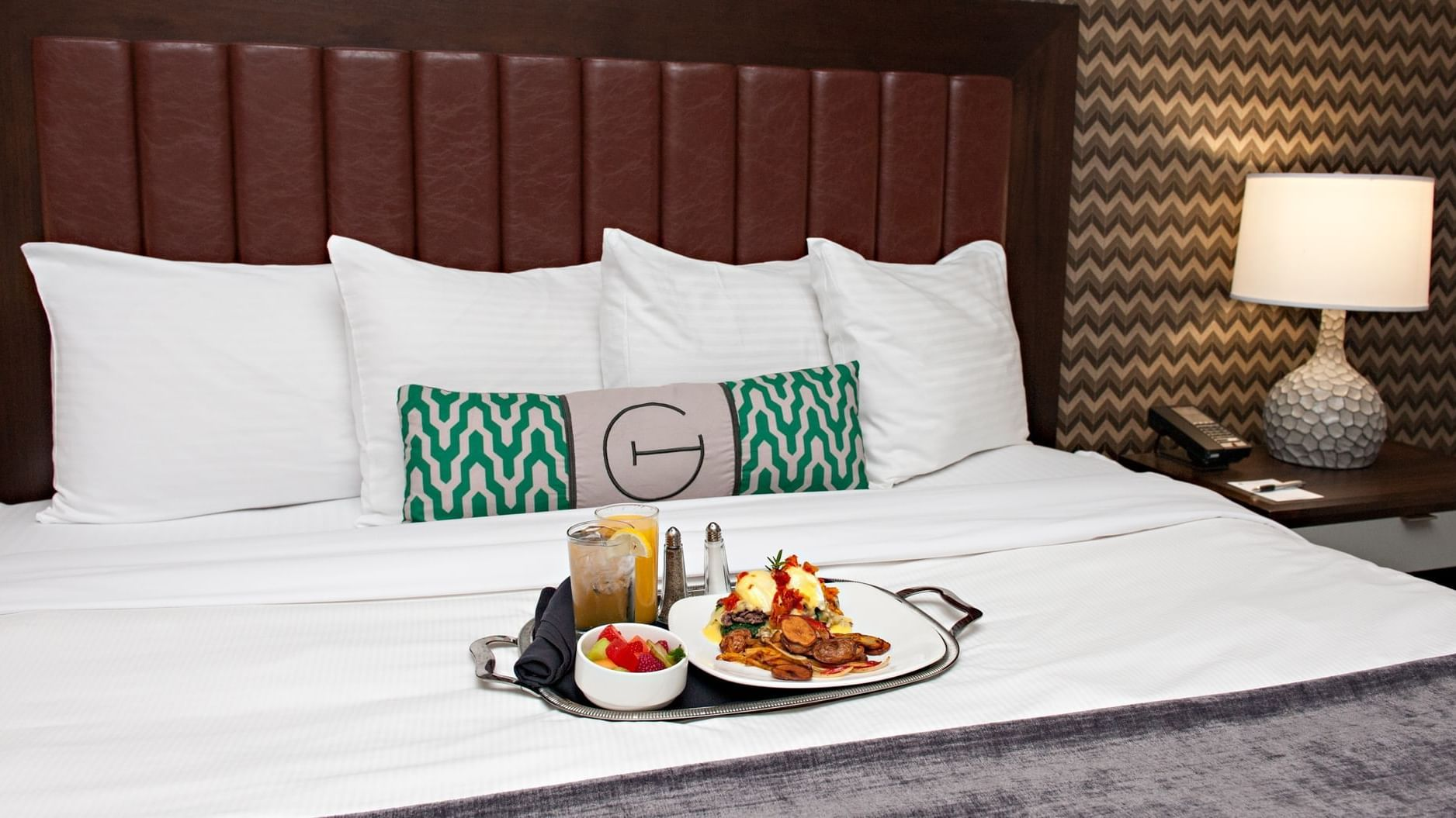 a tray of breakfast on a hotel bed