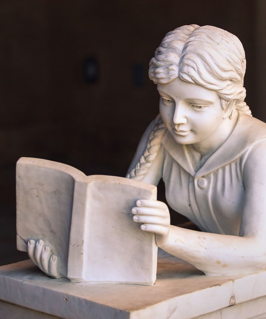 Stone sculpture of a women laying on her stomach reading