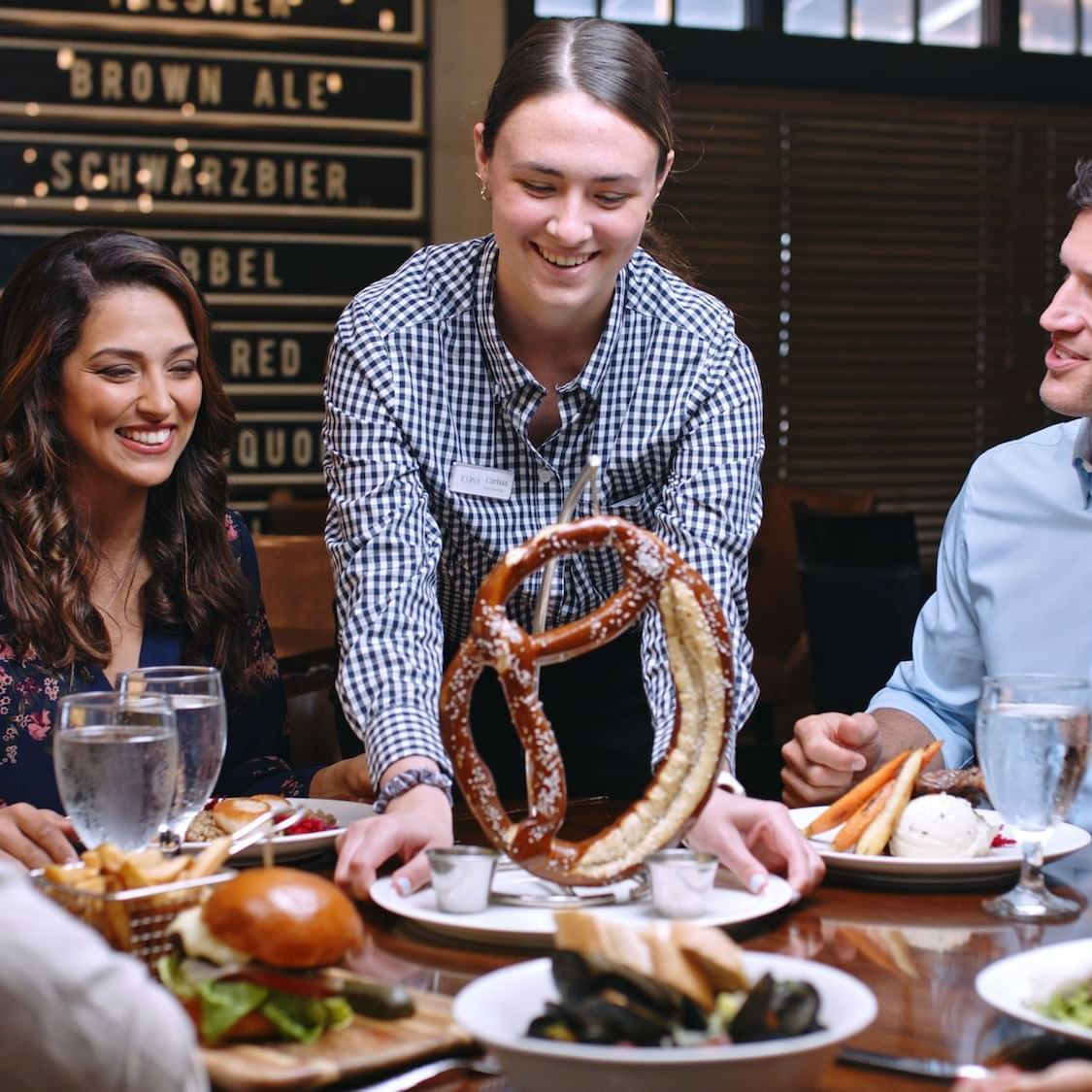 couples enjoying dinner at Avalon Brew Pub, server is smiling and presenting a giant Bavarian pretzel to the table