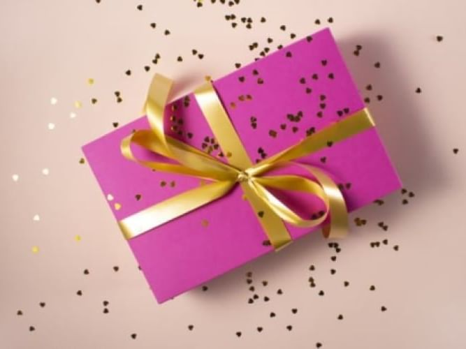 A closeup picture of a purple gift tied from a gold ribbon