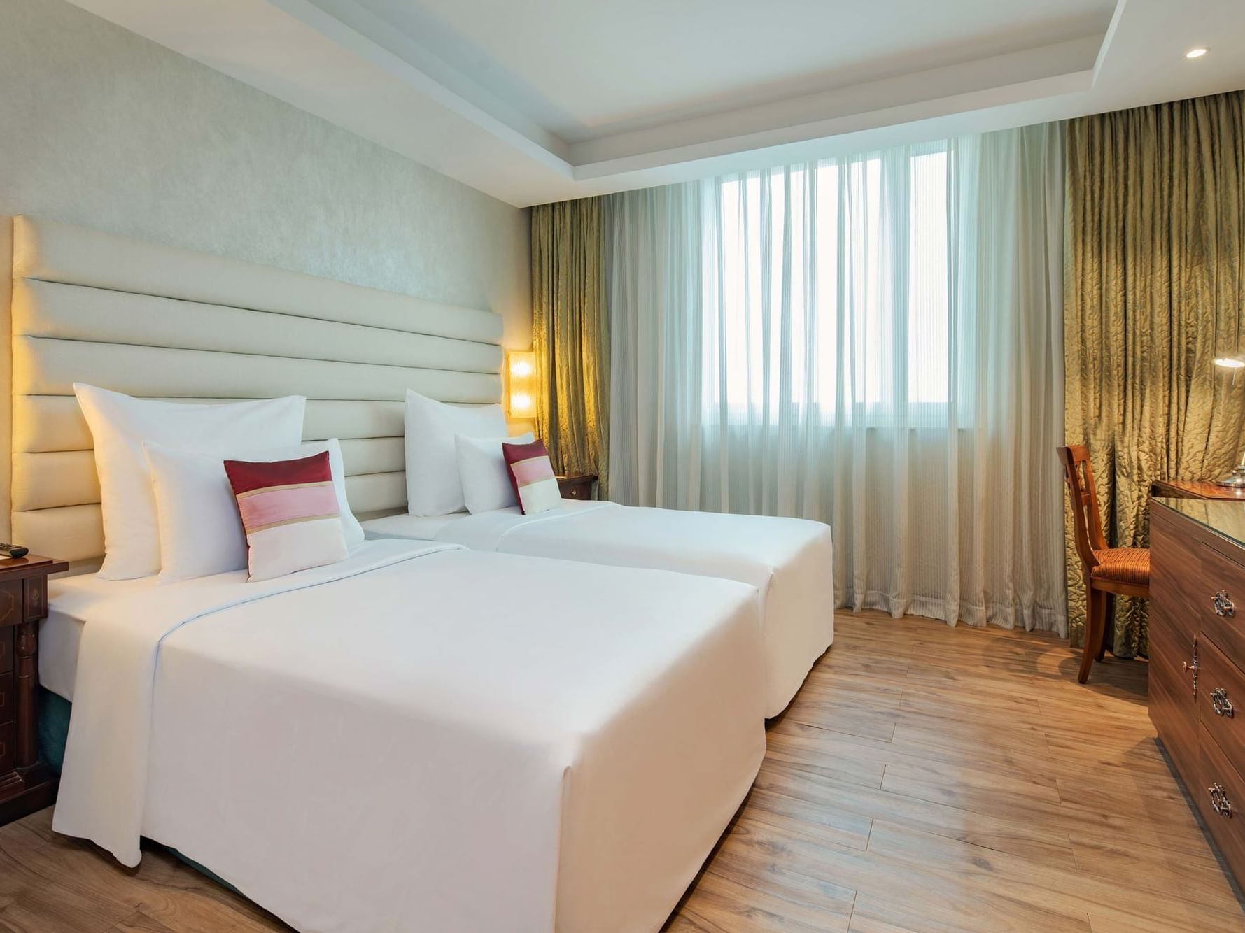 spacious hotel room with combined twin beds and television in front