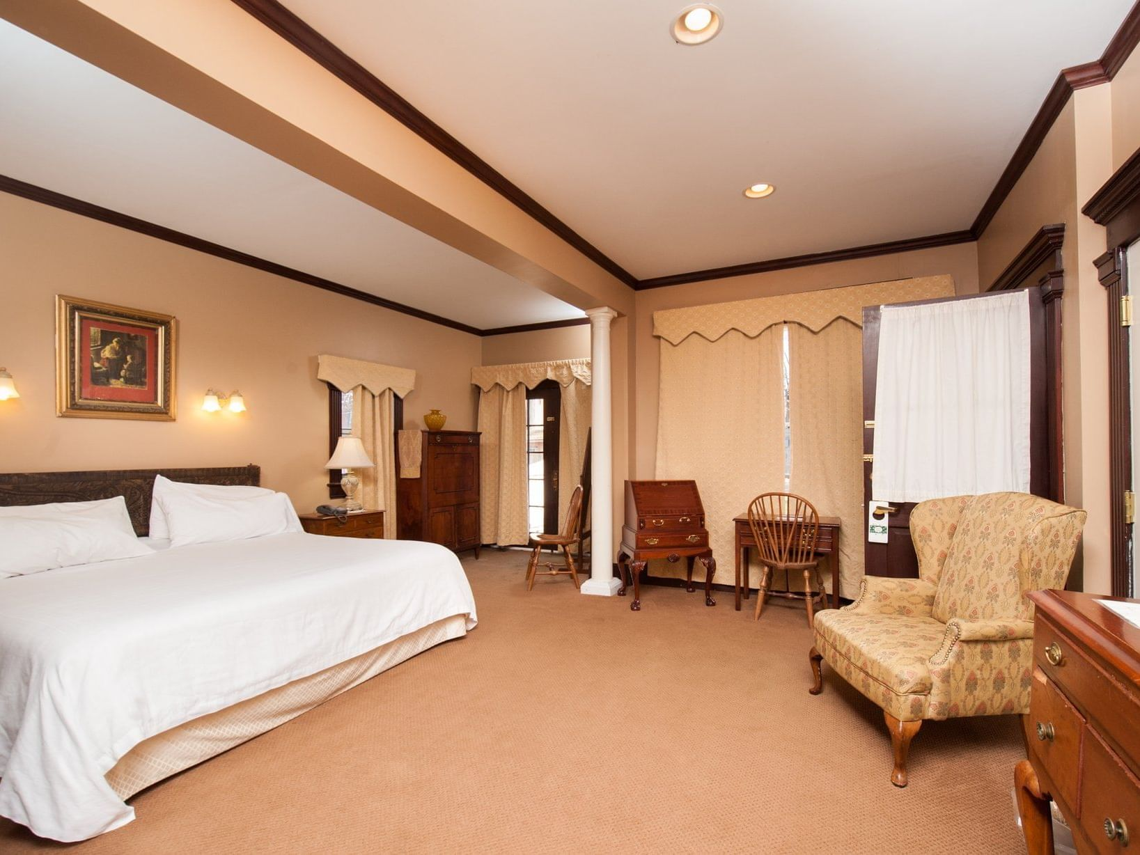 room with large bed, several sitting areas and dressers
