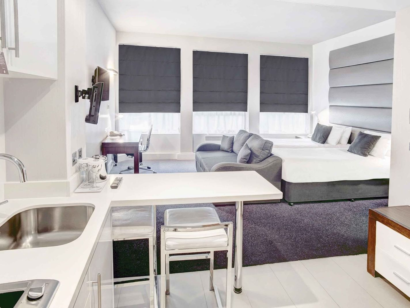 The Two Single Beds Studio at Sandman Signature Newcastle Hotel with two single beds (with premium pillow-top), one pull-out sofa bed, a flat-screen tv and a pantry with white pantry cupboards and furniture