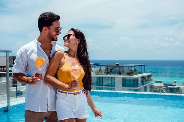 A couple having drinks on pool deck at The Reef 28