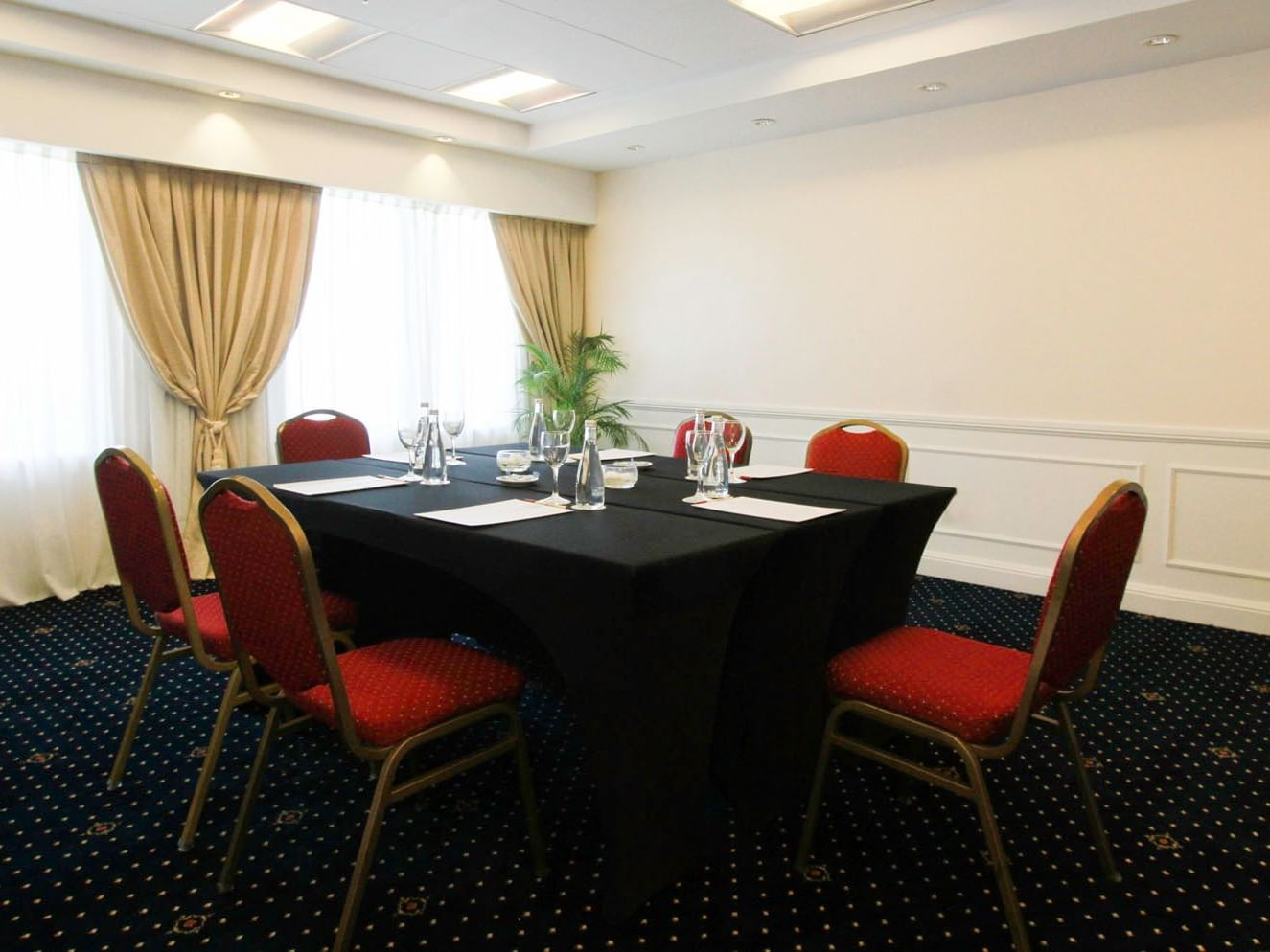 Alcala meeting room arranged with tables and red chairs at Hotel Emperador Buenos Aires