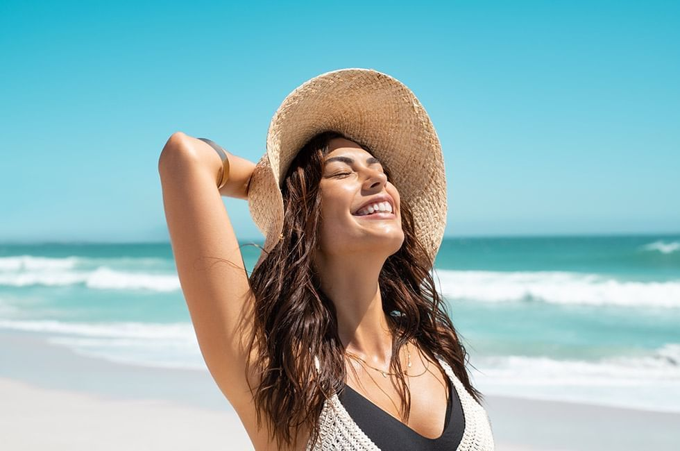 Woman enjoying sun bath on beach at The Reef Playacar