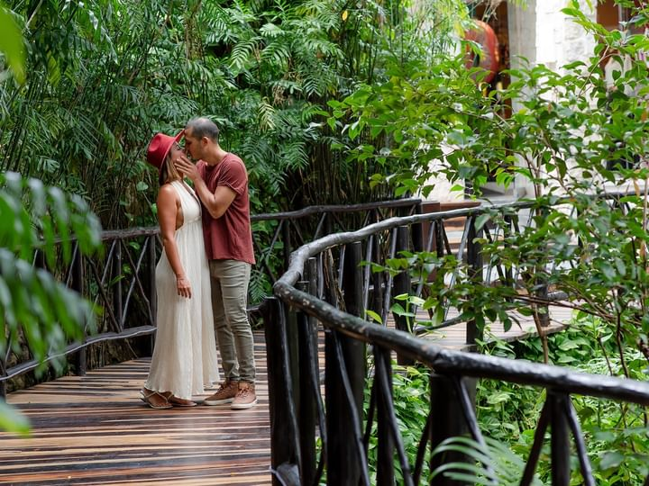 A couple kissing on wooden bridge at The Reef Playacar