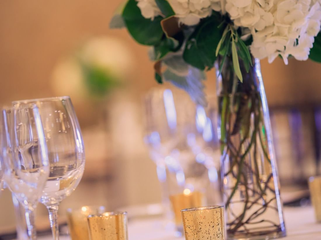 Banquet table set up with flower arrangement, wine glasses, and candles