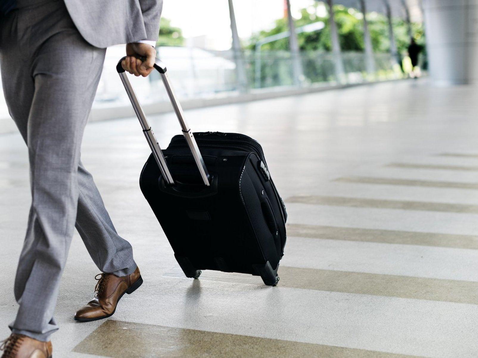 man rolling suitcase