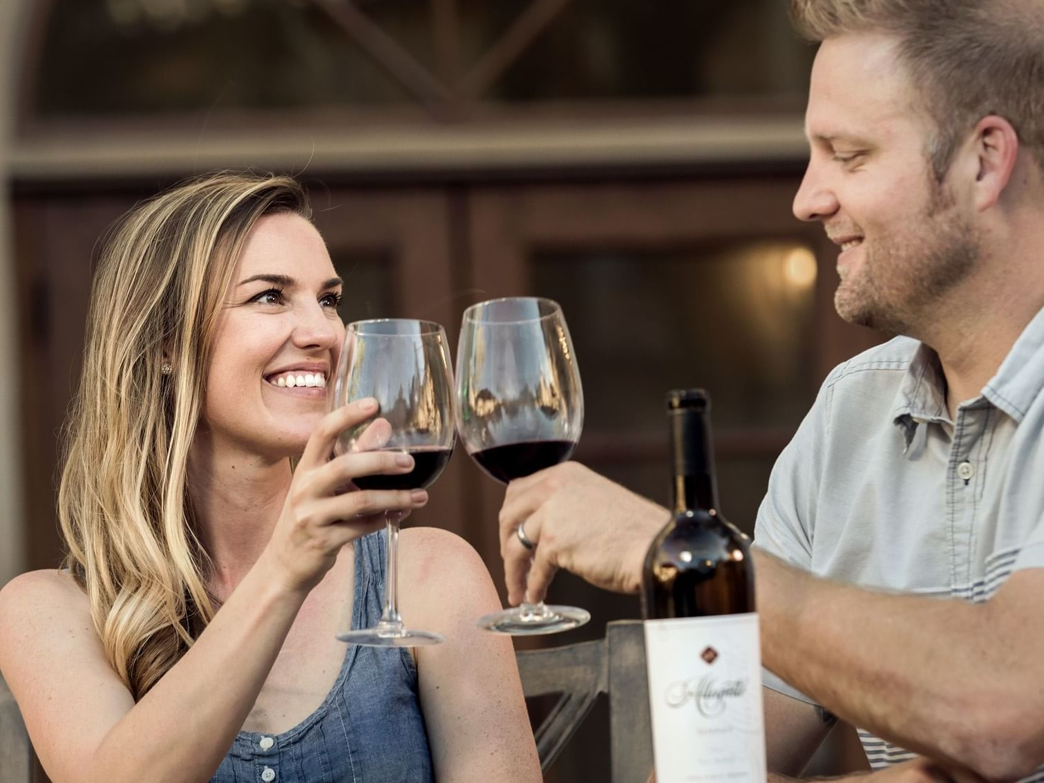 Woman and man toasting with wine glasses