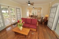 Living room with patio doors to private balcony at Waimea Plantation Cottages