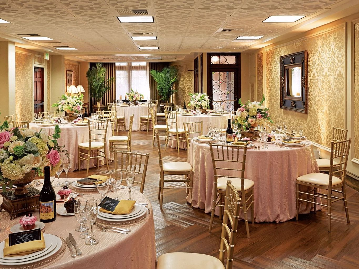 room with round tables wih pink tablecloths and gold chairs