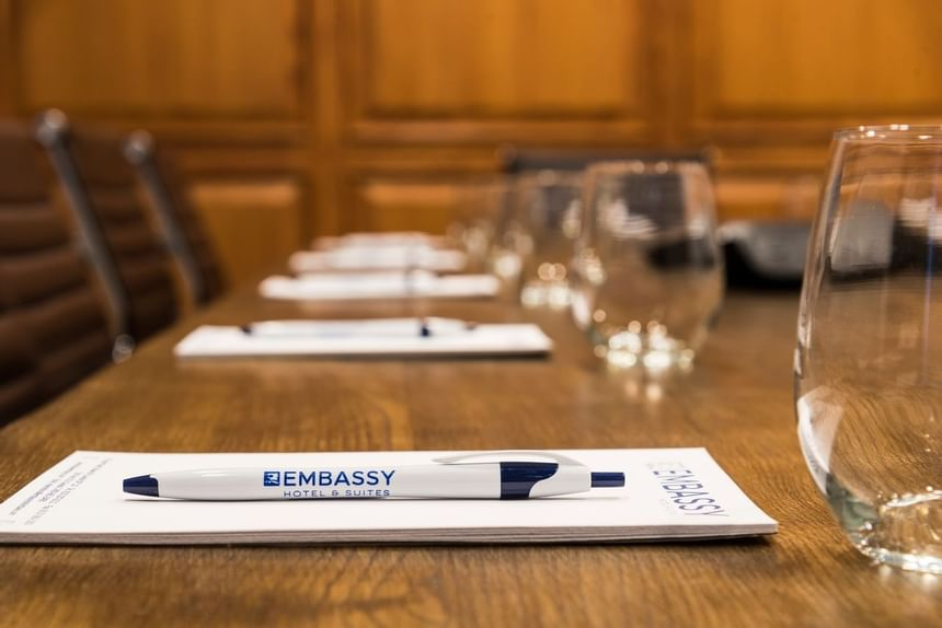 boardroom table with embassy notepads and pens for every chair