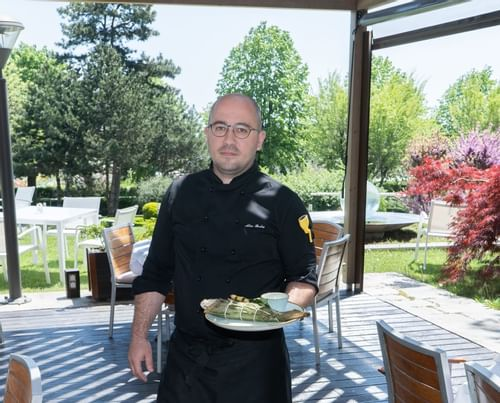 A Chef Holding a dish at Ana Hotels in Romania