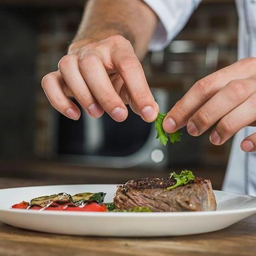 a chef adding garnish to a steak