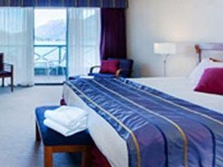 bed in hotel room with balcony overlooking ocean