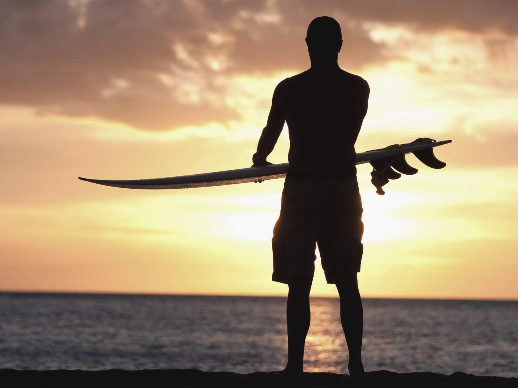 silhouette of man holding surfboard at sunset