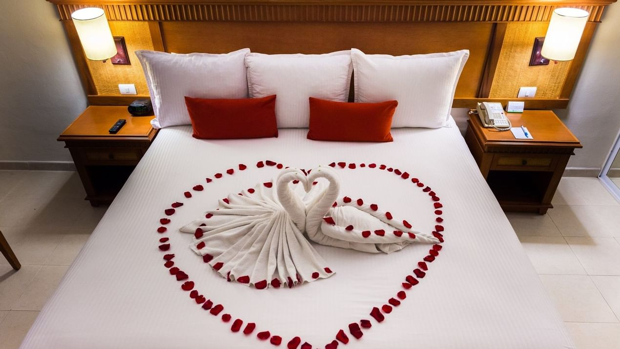 Bed with rose petals in Premium Room at The Reef Coco Beach