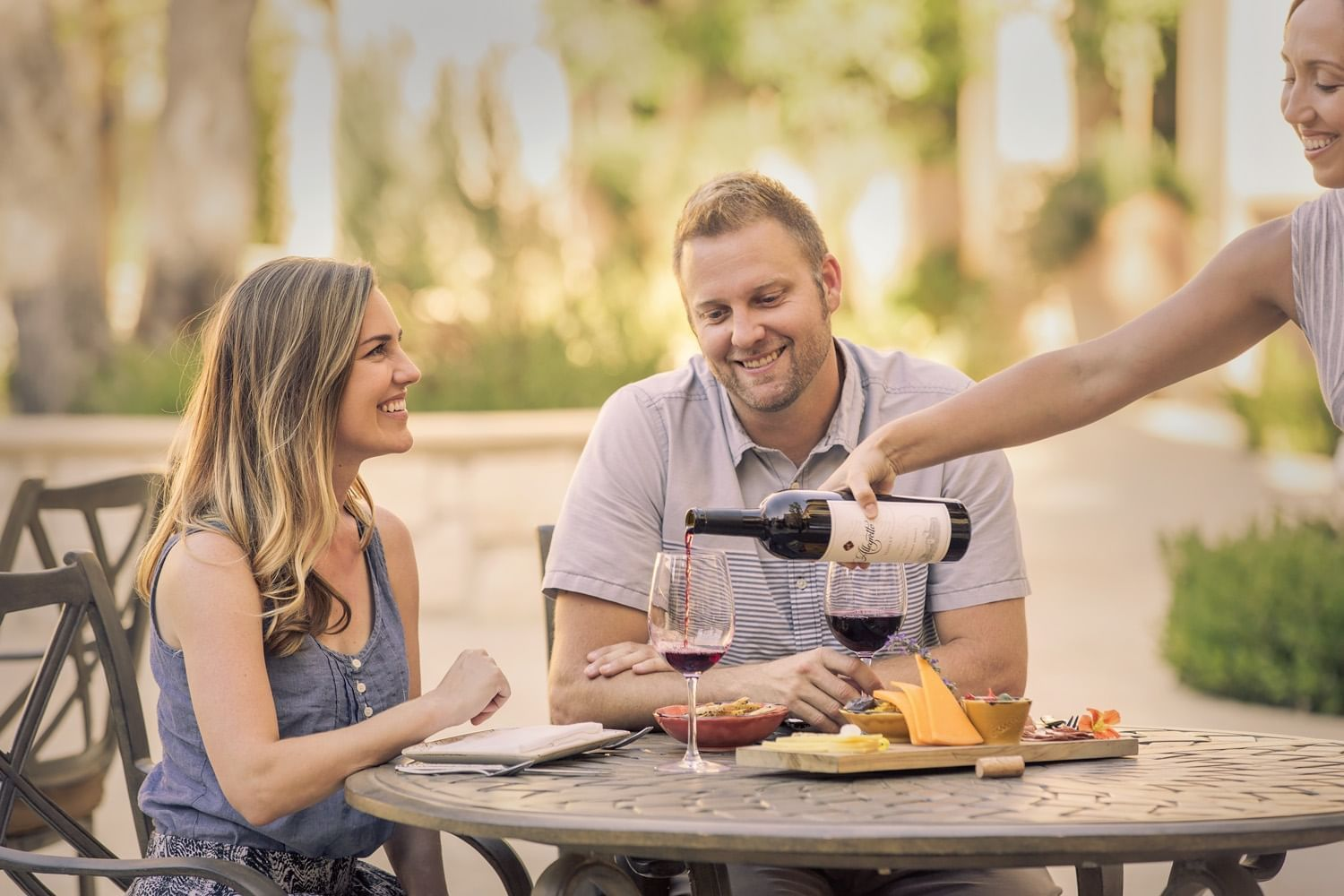 A couple enjoying Allegretto's red wine and cheese platter.