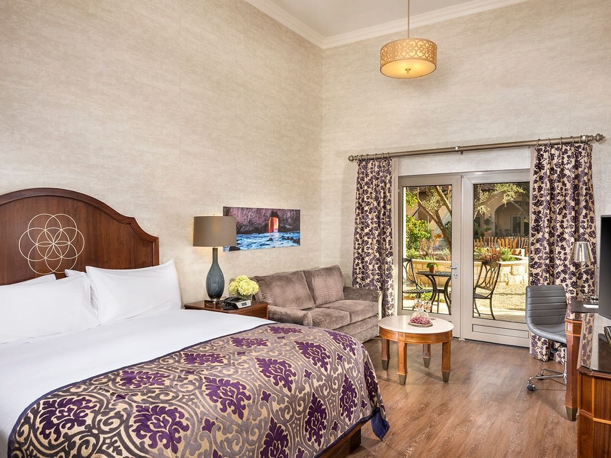Room with king size bed, bench, and glass door to terrace