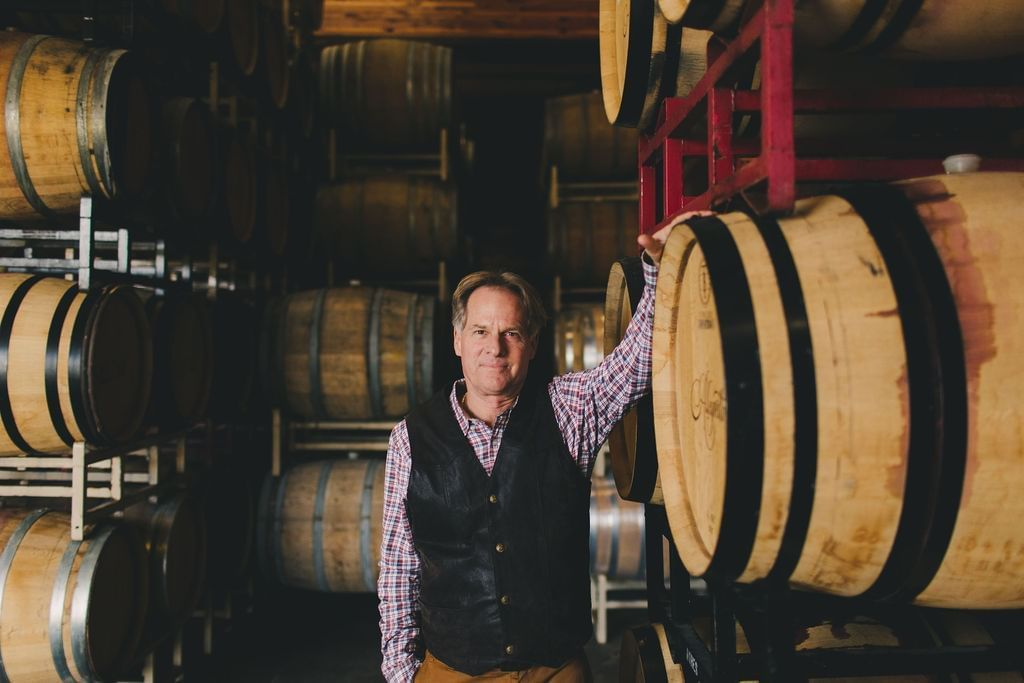 Man leaning against wine barrel