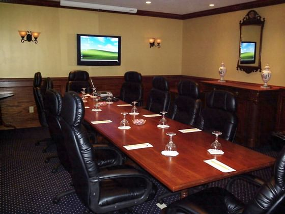 meeting room with table, desk chairs and television on wall