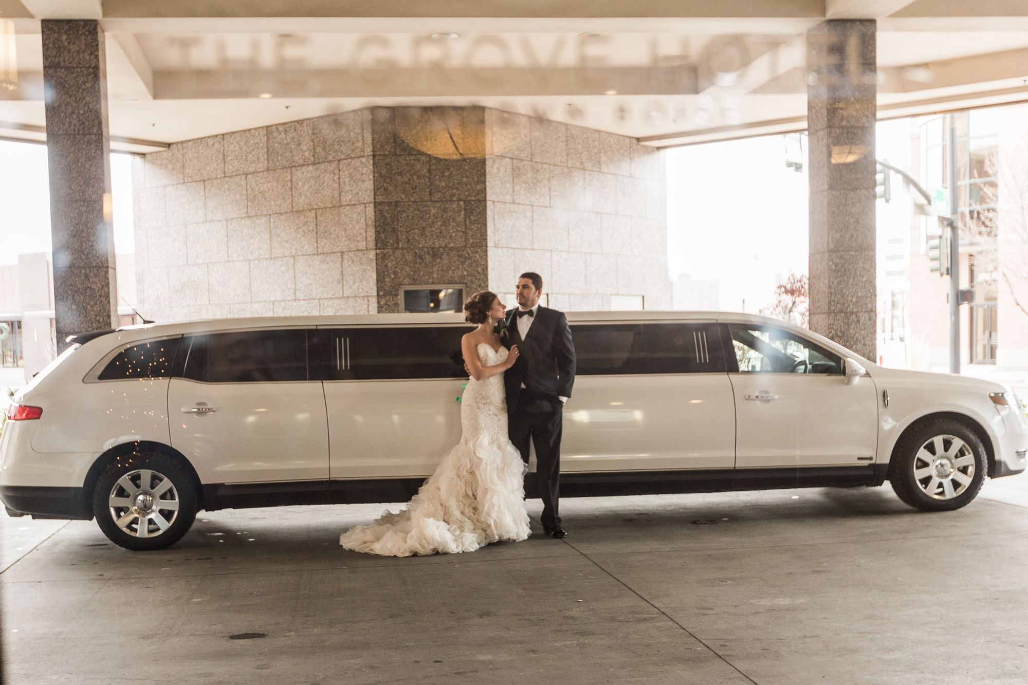 a bride and groom in front of a limo
