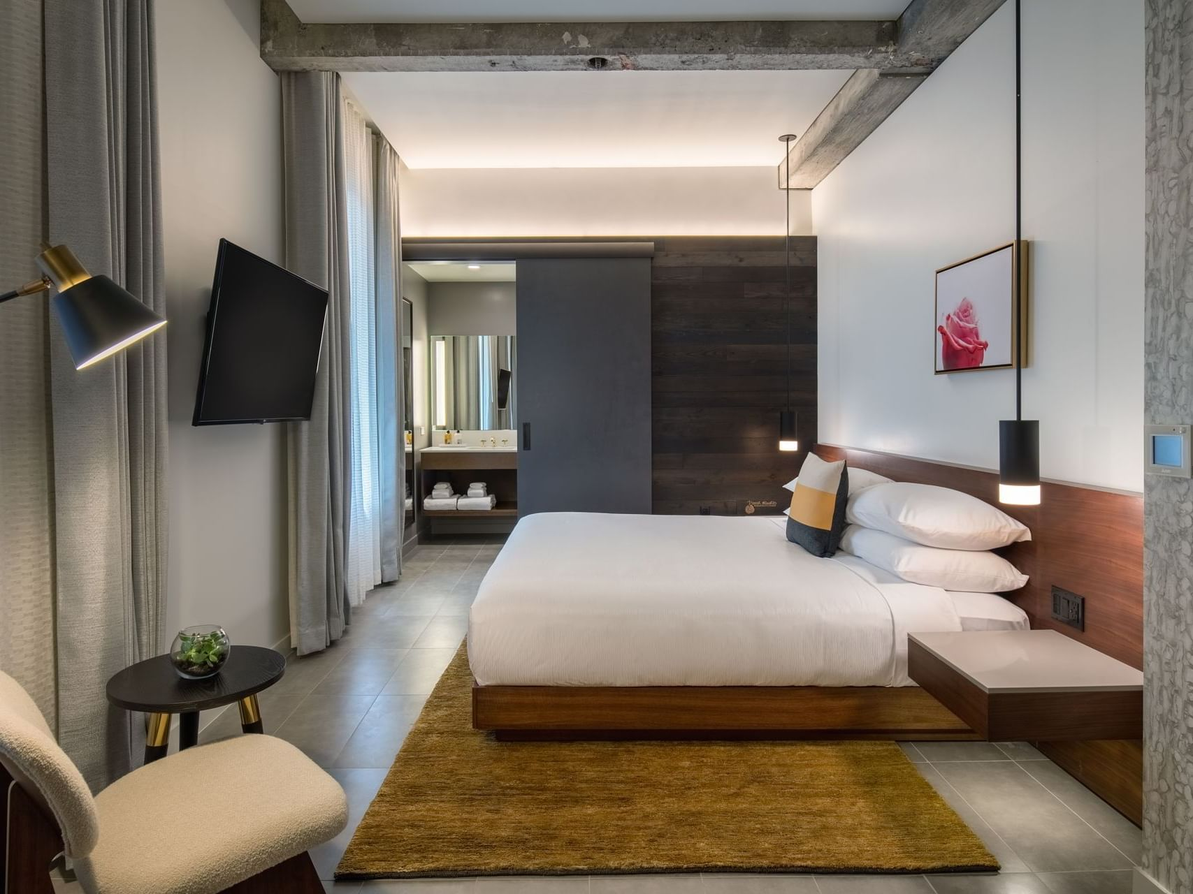 Hi-Lo hotel room with bed and television mounted on wall