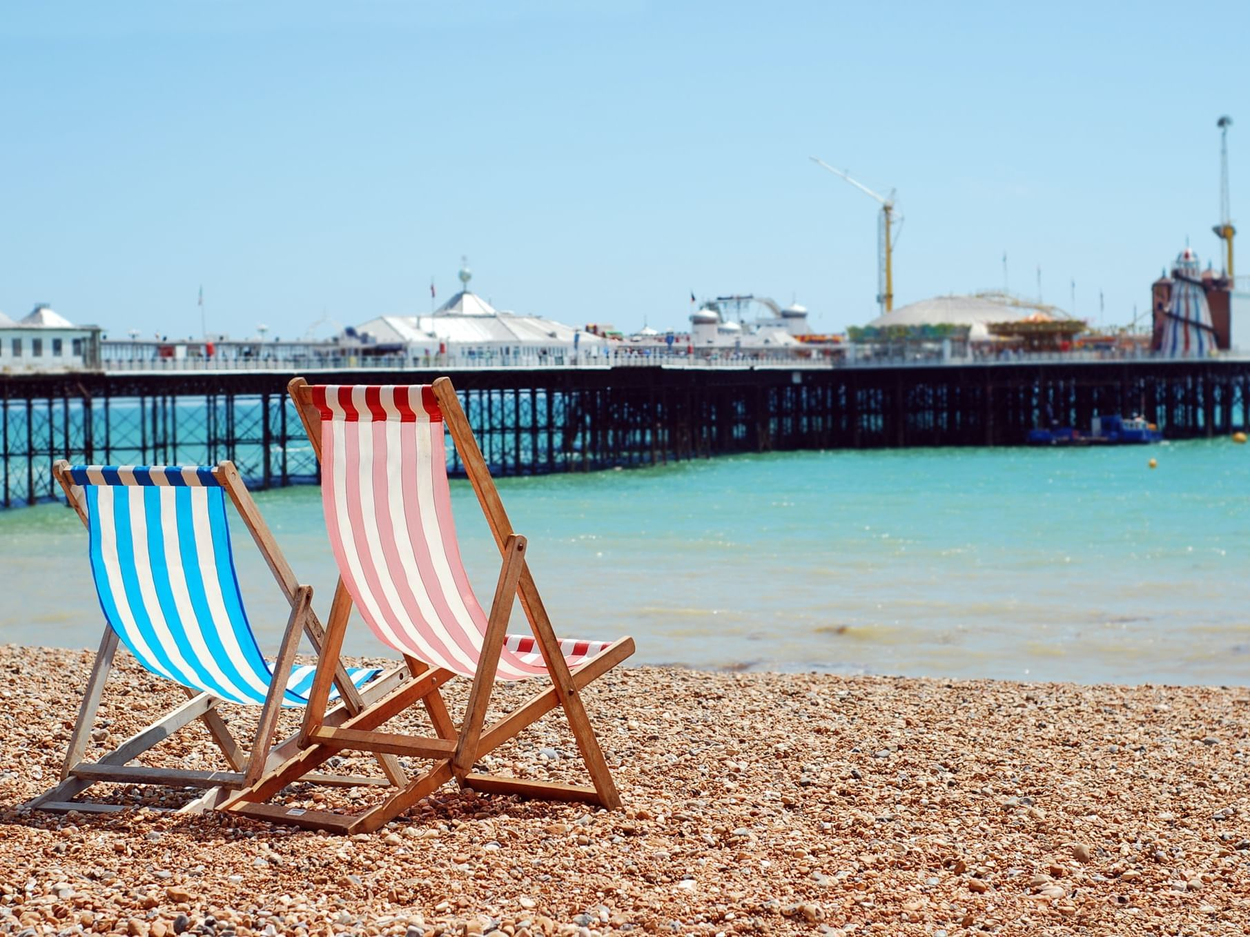 Two beach chairs at the coast of the beach facing the Brighton Palace Pier