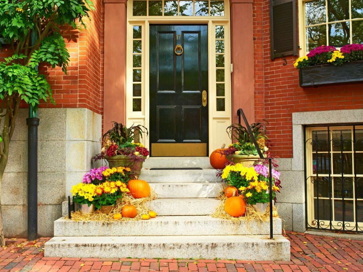 Pumpkins and Fall flowers on the stoop of a red brick building