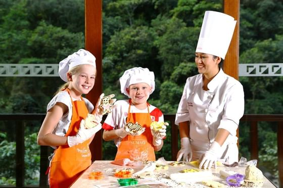 A chef and two kids in aprons making cookies at Hotel Sumaq
