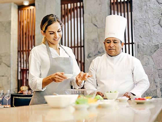 A chef guiding a lady with an apron to cook at Hotel Sumaq