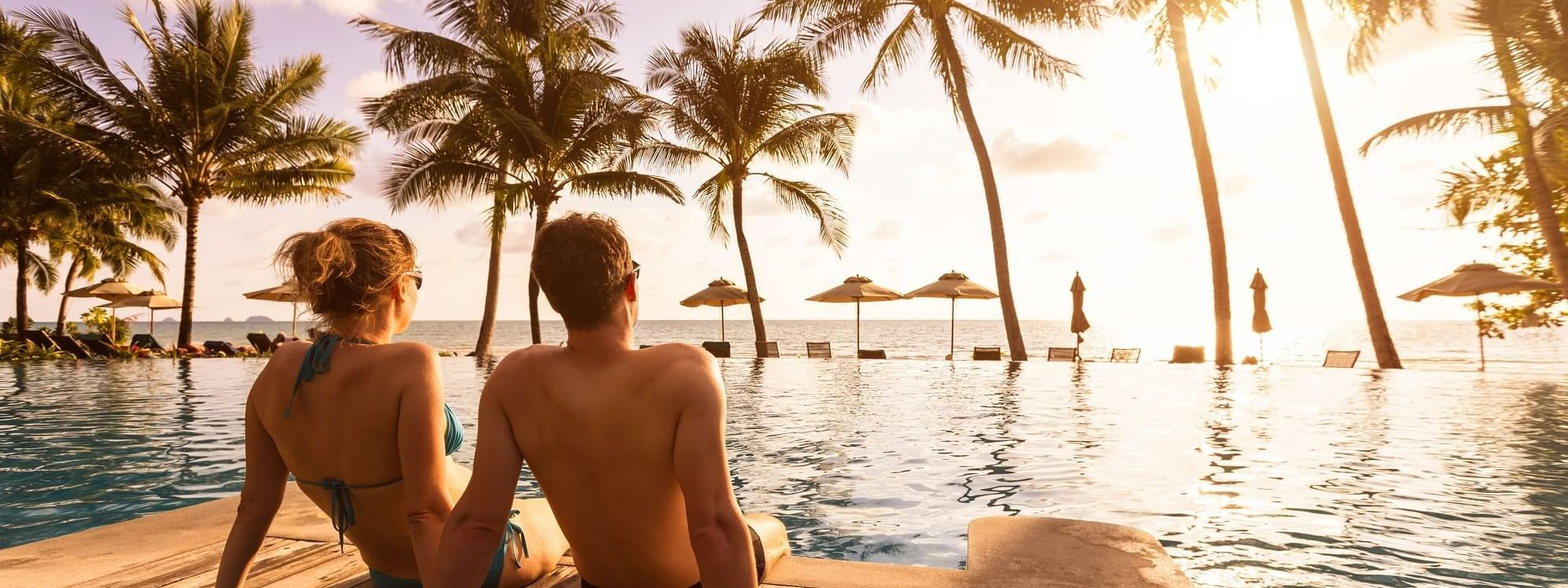 Couple watching sunset from pool deck at Daydream Island Resort