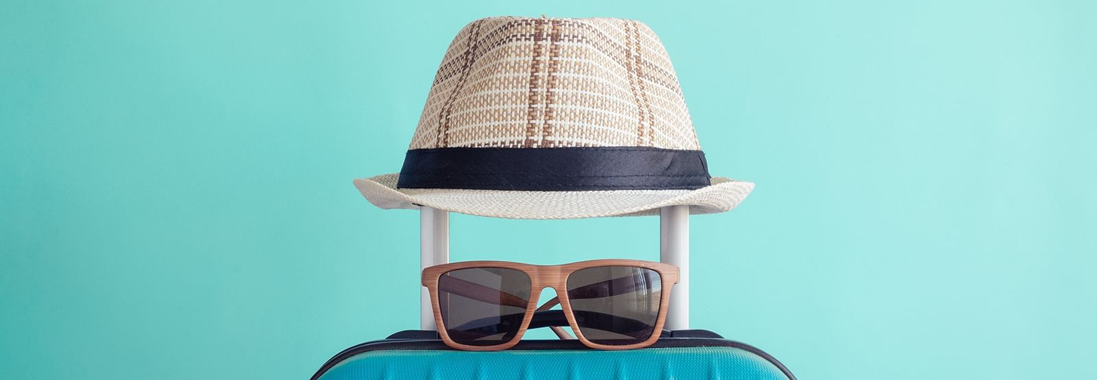 a hat and sunglasses on a rolling bag