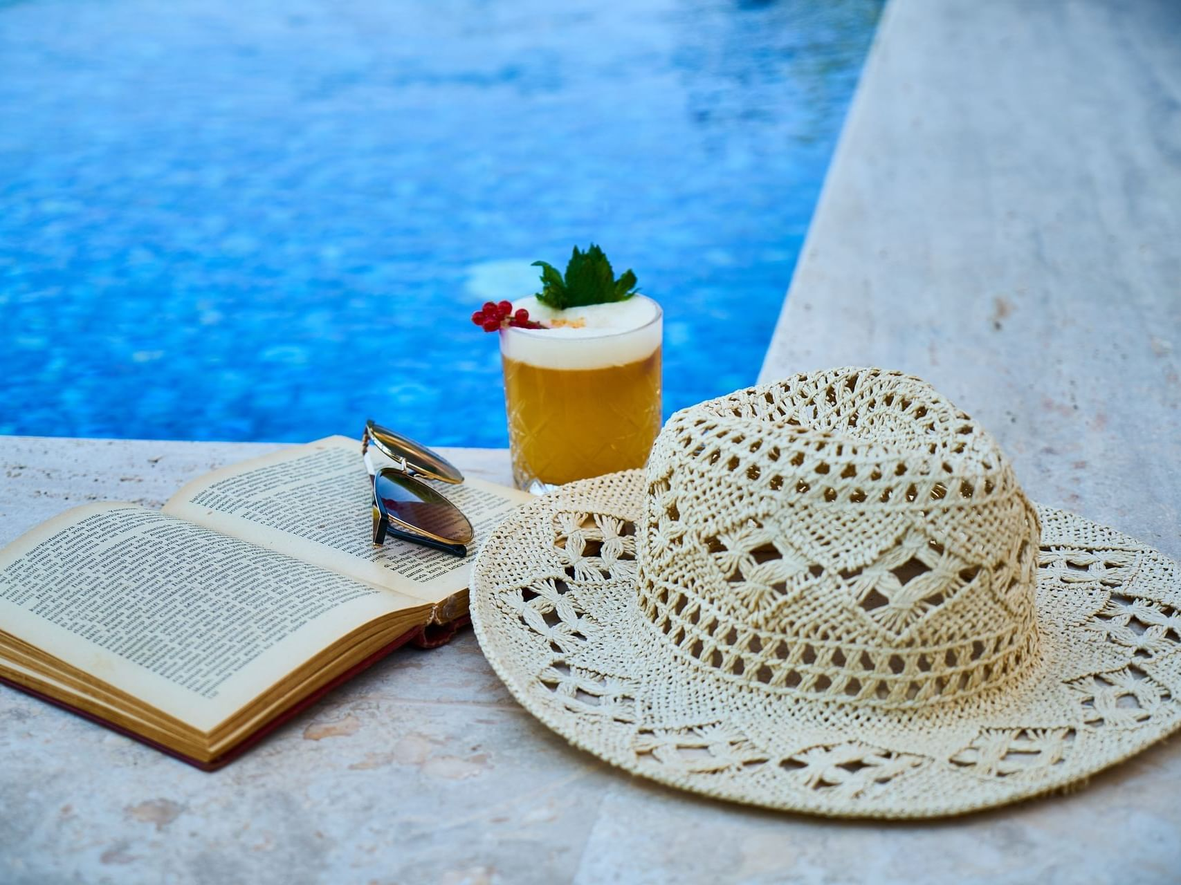 A Hat, book, & a drink on the pool corner at Bay Club Hotel