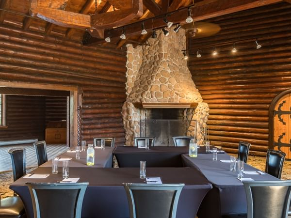 Square conference table in front of large stone fireplace