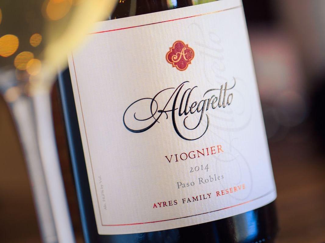 Close up of wine glass and bottle of Allegretto's Viognier wine