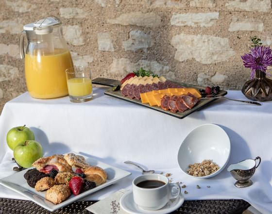 juice, fruit, and pastries at a breakfast buffet