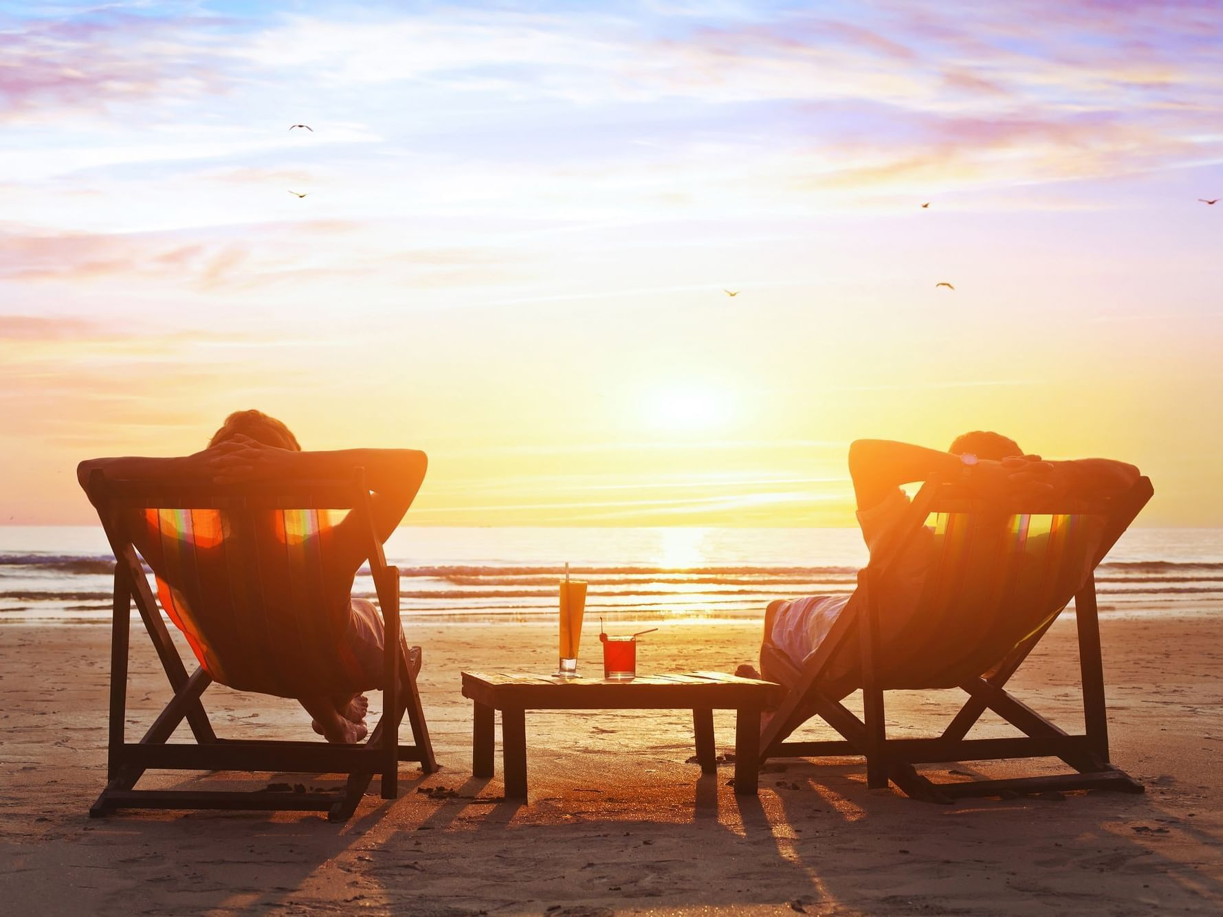 Couple watching sunset from beach at Daydream Island Resort