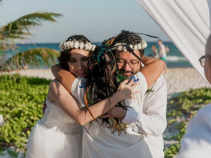 A girl hugging the couple in beach wedding at The Reef Playacar