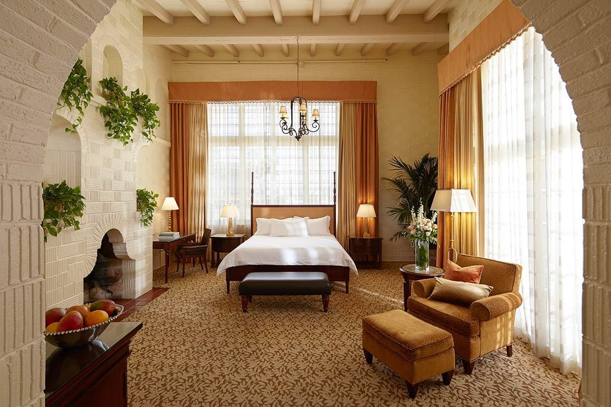 room at Mission inn with large bed, fireplace and accent chair