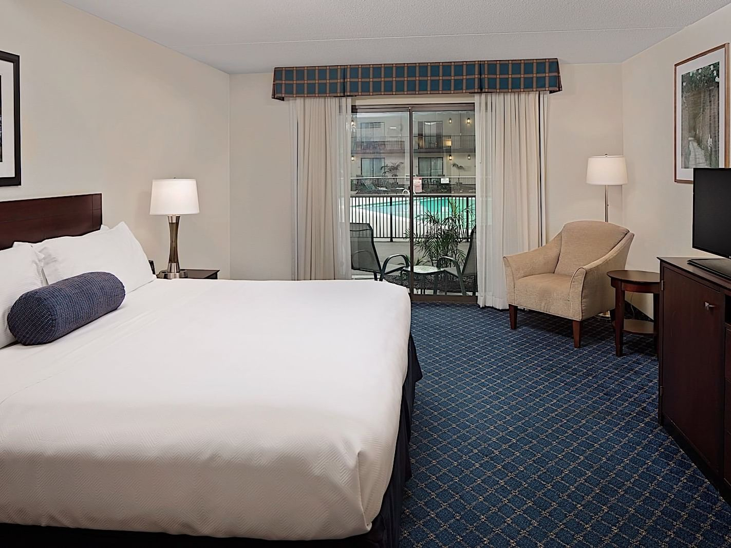 king bed with white sheets in hotel room with blue carpet and view of indoor pool